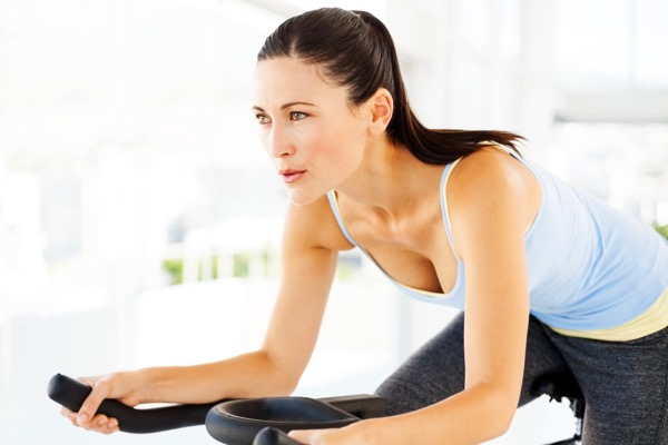 Young Woman Dressed In Workout Clothes Riding An Exercise Bike