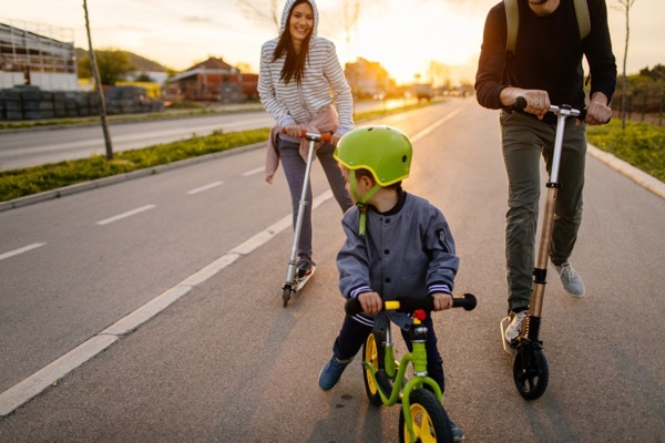 Young family with one child, being active on their push scooters and bicycles